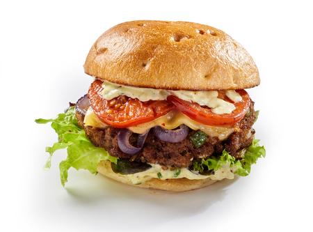 Heerlijke runderhamburger met volledige toeters en bellen, waaronder slaingrediënten, kaas en mayonaise op een knapperig vers wit broodje dat op wit wordt geïsoleerd