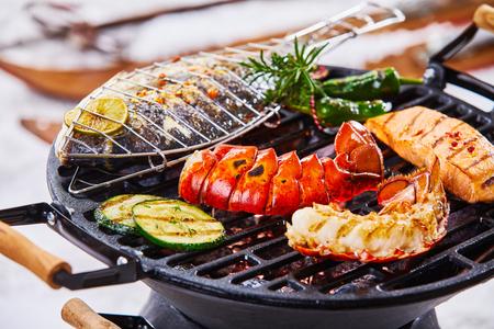 Wintergrill mit Gourmet-Meeresfrüchten, die über den heißen Kohlen grillen, darunter ein Hummerschwanz, Lachs und ganzer Meeresfisch, gewürzt mit Kräutern