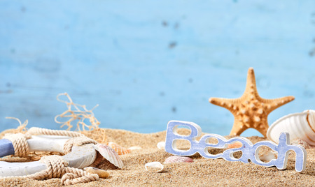 Beach still life with seashells , a starfish, life ring and text on golden sand and copy space on a blue background Stock Photo