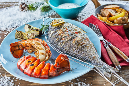 Close up view of barbecued fish on plate with lobster