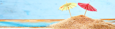 Close-up of two cocktail umbrellas on sand as summer vacation banner or concept for romantic destination at the seaside
