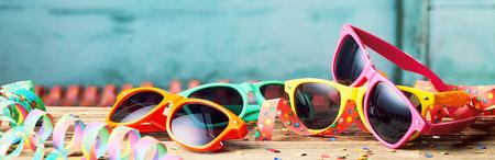 Large vue en angle des lunettes de soleil colorées et des banderoles de fête, fond sur le thème du carnaval