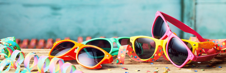 Wide angled view of colorful sunglasses and party streamers, carnival themed background Stock Photo