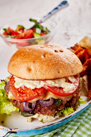 Traditional hamburger with all the trimmings including melted cheese, tomato, lettuce, onion and mayonnaise served in an old vintage dish with a side salad Stock Photo