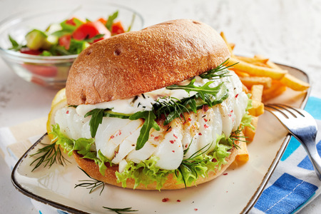 Healthy fresh seafood burger with fish fillet dressed with mayo and rocket and seasoned with spice