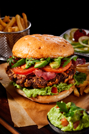 Wholesome gourmet burger with avocado, crispy bacon and guacamole on a juicy meat patty served on brown paper with side dishes