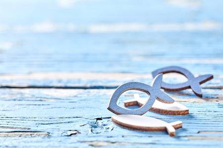 Wytnij kształty ryb na zwietrzałym niebieskim drewnie za pomocą łuszczącej się farby z widokiem na ocean z przestrzenią do kopiowania