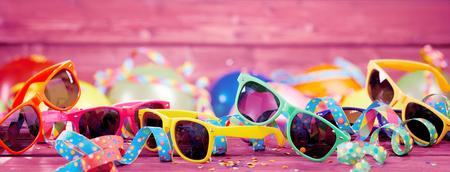 Partijbanner met kleurrijke confettien, wimpels en plastic zonnebril op roze houten raad met exemplaarruimte Stockfoto