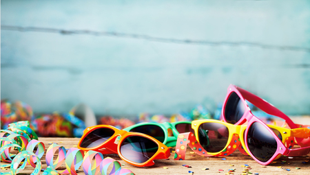 Colorful sunglasses and party streamers, carnival themed background