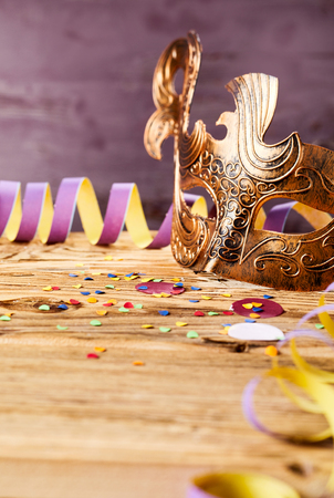Carnival background with golden mask and a coiled purple streamer on wood with scattered confetti and copy space