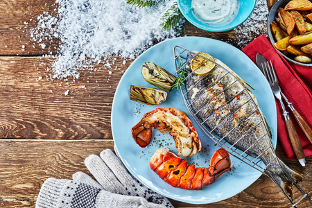 High angle view of barbecued fish on plate with crayfish against table