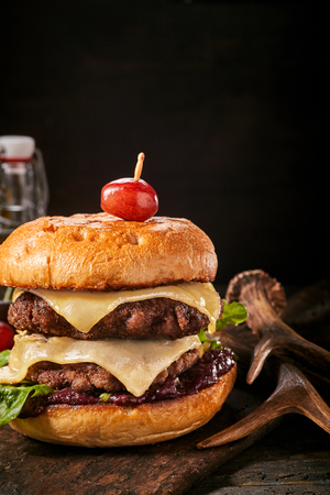 Double decker cheesy venison burger with melting cheese on ground deer meat alongside a pair of antlers on rustic wood with copy space above over black Stock Photo