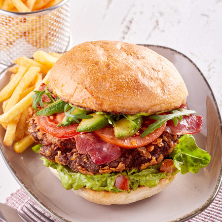 Guacamole burger with fresh avocado pear and crispy fried bacon served with French fries on modern pottery plate Stock Photo