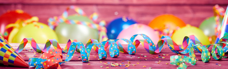 Colorful festive party or carnival banner with twirled streamers, confetti and balloons on a pink background Banco de Imagens