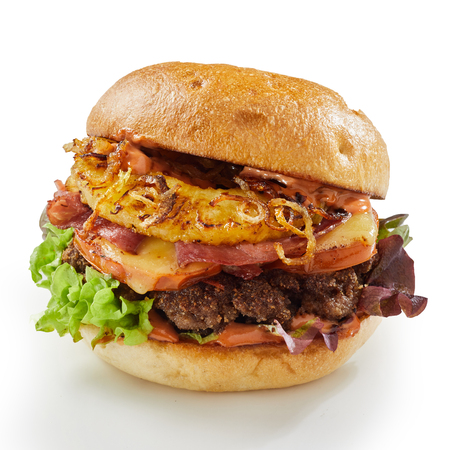 Pineapple and ham beef burger with fried onion and melted cheese on a crusty bun isolated on white