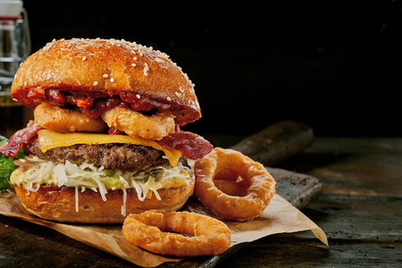 Gourmet Surf and Turf burger with squid rings, crisp bacon, beef patty and cheese served on a rustic wooden board over a dark background with copy space Stockfoto