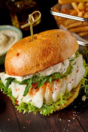 Visburger met mayonaise op een bedje van sla gekleed met verse rucola en dille geserveerd op een knapperig wit broodje Stockfoto