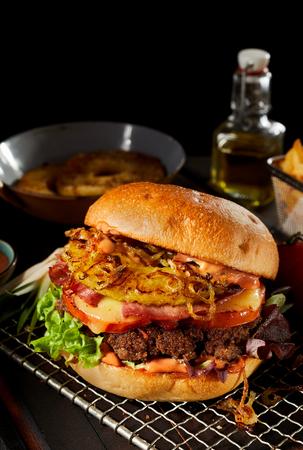 Savoureux hamburger hawaïen grillé avec ananas, fromage et jambon sur une galette de b?uf juteuse debout sur une grille dans une cuisine Banque d'images - 93272211