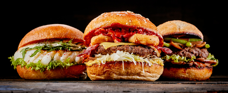 Close-up of three different tasty hamburgers with fish, beef meat or cheese on a wooden table against black background for copy space