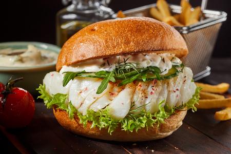 Burger de poisson en bonne santé avec mayonnaise, roquette, laitue et vinaigrette mayo sur un petit pain croustillant
