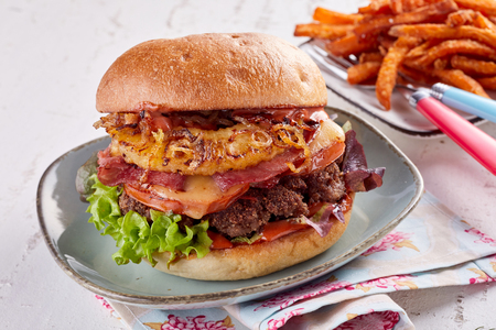 Hawaiian burger with ham, cheese and pineapple topped with fried onions on a fresh crusty bread bun served with crispy vegetable chips