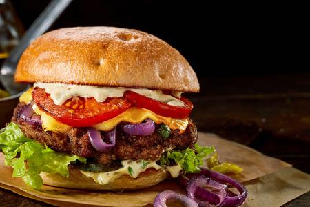 Lekkere traditionele Amerikaanse cheeseburger met verse salade ingrediënten en mayonaise op een vers knapperig geroosterd broodje met kopie ruimte over zwart Stockfoto