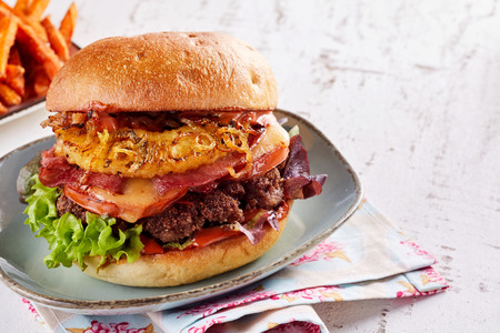 Grand hamburger hawaïen appétissant avec bacon, ananas et jambon sur une galette de b?uf servi sur une plaque de poterie vintage avec espace copie Banque d'images - 93272214