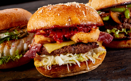Tasty barbecued surf and turf burger with beef, fried squid, bacon and cheese dressed with ketchup on a crusty bun
