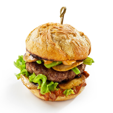 Savory mushroom burger with sliced fungi layered over a thick succulent beef patty isolated on white