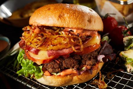 Heerlijke zelfgemaakte cheeseburger of publunch met een dikke sappige runderpasteitje en garnituren van salade op een rooster