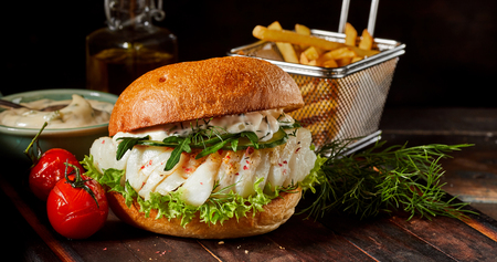 Gourmet seafood codfish burger with fish fillets dressed with spice, mayonnaise, fresh rocket and lettuce served on a toasted bun with French fries