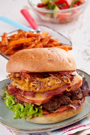 Appetising Hawaiian pineapple and ham beef burger with salad ingredients and melted cheese served on a plate with vegetable chips to the side