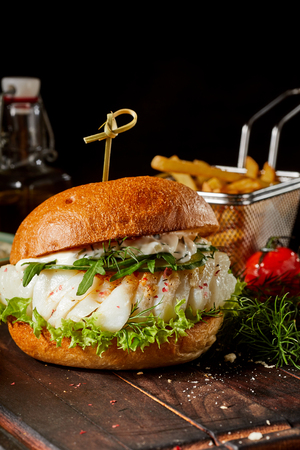 Gourmet fish burger with fresh rocket, dill and mayonnaise served on a rustic table with a wire basket of French fries