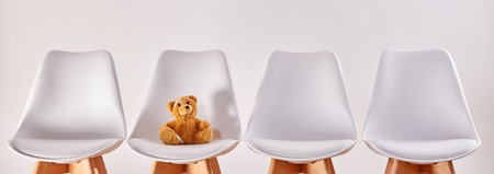 Cute brown teddy bear on a seat in the waiting room with empty chairs of a hospital or a health center for children 스톡 콘텐츠