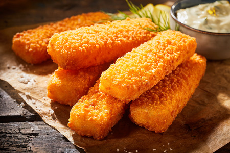 Close up view of crispy deep fried fish fingers with breadcrumbs served with sauce Foto de archivo