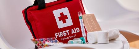 Kit de primeiros socorros vermelho pequeno com pílulas, bandagens e um termômetro no assento de uma cadeira em um conceito de triagem e cuidados de saúde Foto de archivo