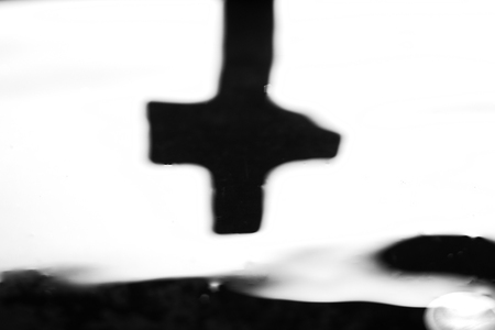 Spiritual concept with defocused black cross against white background Stock Photo