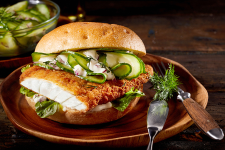 Delicious seafood burger with a crumbed fish fillet, cucumber and baby spinach on a plate with utensils over a rustic wood background