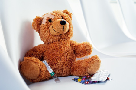 Cute little teddy sitting on a chair with a plaster on its head, hypodermic syringe and pills or medication in a medical and healthcare concept