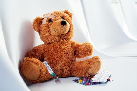 Jolie petite peluche assise sur une chaise avec un pansement sur la tête, une seringue hypodermique et des pilules ou des médicaments dans un concept de médecine et de soins de santé Banque d'images - 93636990