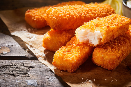 Close-up of delicious deep fried fish fingers served on paper on a rustic wooden table