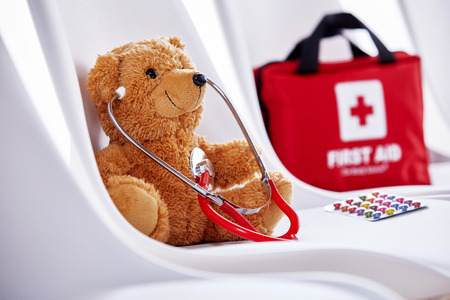 Medical concept of teddy bear with stethoscope sitting on chair with first aid kit in background