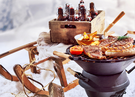 Winter barbecue outdoors in the snow with T-bone steaks and sausages sizzling on the grill and a crate of beers on a wooden sled