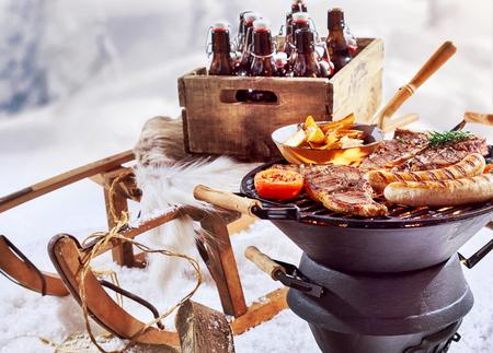 Winterbarbecue buiten in de sneeuw met T-bone steaks en worsten die sissen op de grill en een krat bier op een houten slee