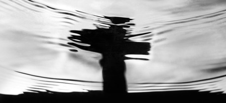 Panoramic banner of a cross gravestone reflected in rippling water for concepts about bereavement, loss, death and mourning