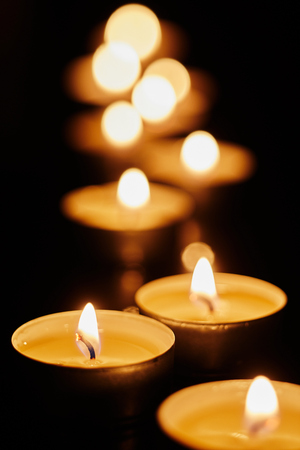 Votive candles burning in the darkness in a church or during a remembrance vigil at night with shallow dof and background bokeh Banco de Imagens