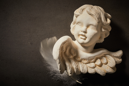 Spiritual concept of angel figurine with feather against dark background