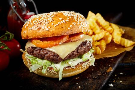 Originele Amerikaanse cheeseburger met friet en salade garnituur op rustiek hout met ketchup en tomaten aan de zijkant