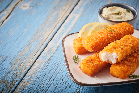 Dish of fishfingers with sauce dip on rustic blue wood background with copy space.