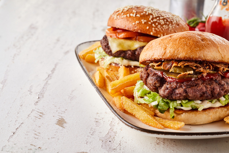 Close-up of two tasty hamburgers with beef ground meat served with French fries on a tray on a white wooden table